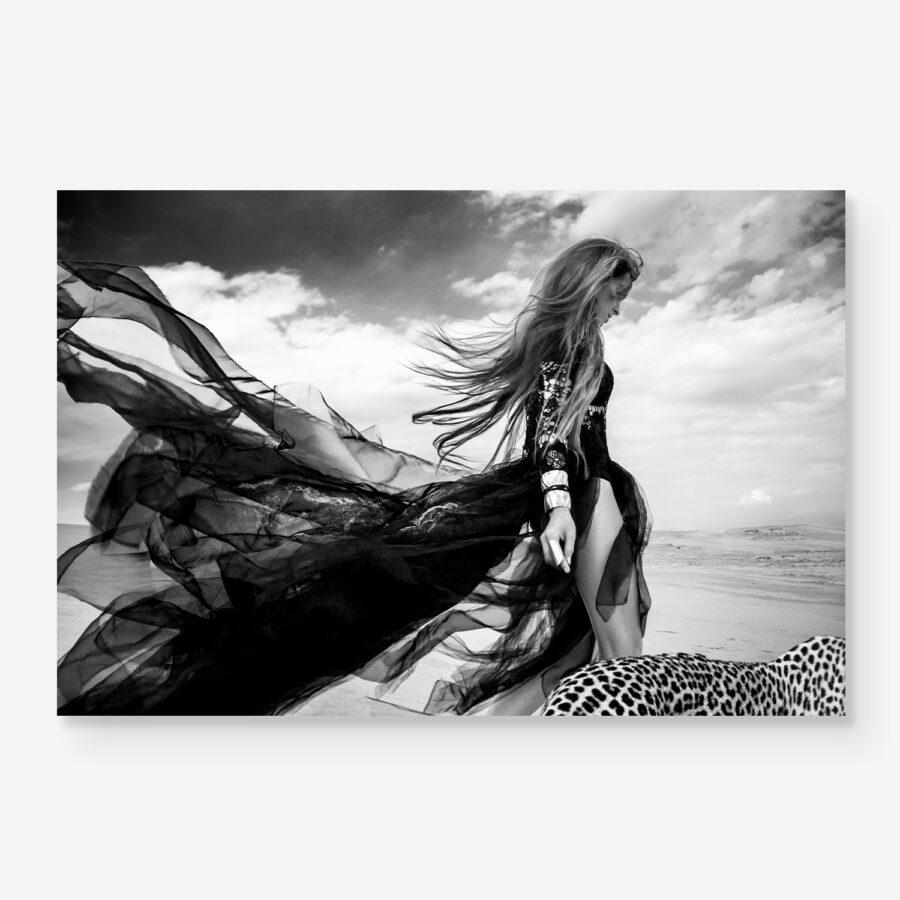 model in black dress walking with leopard